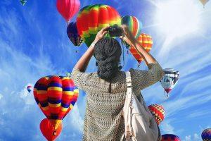woman taking photos of hot air balloon rides